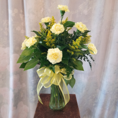 "A simple bouquet of a dozen carnations in either yellow, pink, orange, white, red, hot pink, or mixed colors come with filler and a bow. Approx 25""H x 16""W **Color of container may vary**"