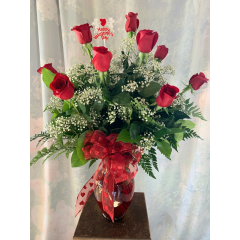 """Beautiful Dozen roses available in only these colors: Red, nicest Pink, Lavender or White in a red vase and topped off with a festive Valentines' Bow. Approx. 30""""H x 22""""W...Also you can upgrade your dozen in a clear keepsake vase for $149.95 and measures approx. 33""""H x 23""""W"""