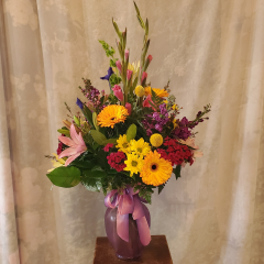 Beautiful variety of mixed flower bouquet in a vase and complimentary bow. **Flowers and color of vase may vary**