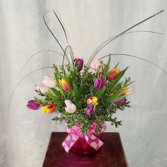 "A beautiful spring bouquet of 20 mixed colored tulips in a hot pink glass vase with festive bow. Approx. 13""H x 13""W"