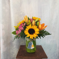 "Fun,Summer Bouquet in a bright colorful mixture of lilies, sunflowers, alstro and solidago in a mason jar with a hello tag. Approx. 14""H x 12""W ***Colors and flowers may vary depending on availability***"