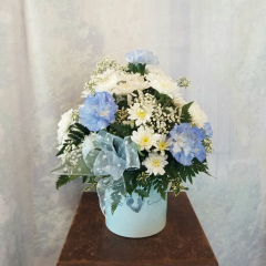 """New to our Baby Collection is our keepsake container that says Love and precious baby footprints to make the """"V"""" in love. Made with Tinted blue carnations, white cushion poms, baby's breath and blue sheer bow with white polka dots. Approx 14""""H x 12""""W"""