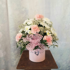 """New to our Baby Collection is our keepsake container that says Love and precious baby footprints to make the """"V"""" in love. Made with Pink carnations, white cushion poms, baby's breath and pink sheer bow with white polka dots. Approx 14""""H x 12""""W"""