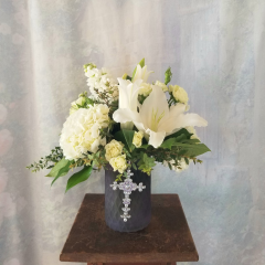 "Getting fresh memorable and special flowers for your loved one or dear friend regardless the occasion. Featuring white stock, white spray roses, white hydrangea and white lilies, our Peaceful Moments Bouquet has just what it takes to show you care! In a frosted, etched purple vase adorned with a jeweled metal cross. Approx. 15""H x 13""W"
