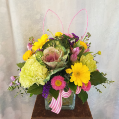 """This bright, colorful bouquet is ready for Easter morning! Like an Easter bunny hiding in a flower arrangement, fun decorative bunny ears are hiding among lively hydrangeas, gerbera daisies, kale, asters, ranunculus, tulips, stock and variegated greens. Send this arrangement to a loved one to celebrate the Easter holiday or add it to your decor for a fresh touch! Approx. 18.5""""H x 18""""W **flowers may be subject to change depending upon availability**"""