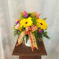 """Spring pops with this bright & colorful bouquet! Bursting with color and fun it features pretty Asiatic lilies, purple asters, gerbera daisies, carnations, kermit poms and don't forget the playful Easter eggs! Delivered in a white basket. Approx. 12""""H x 13""""W."""