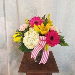 """Fun and festive bouquet with hydrangea, asiatic lilies, gerbera daisies, carnations and iris in a ginger jar style vase with striped ribbon. Approx 14""""H x 13""""W ****Colors of flowers and style of vase may vary depending upon availability***"""