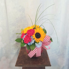 "Cute little bouquet in bright colors of carnations, gerbera daisies, sunflowers and hydrangea in a colored etched bubble bowl finished with a striped bow. Approx. 10""H x 9""W. ***Colors of flowers and vase may vary***"
