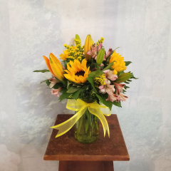 """Fun,Summer Bouquet in a bright colorful mixture of lilies, sunflowers, alstro and solidago in a mason jar with a hello tag. Approx. 14""""H x 12""""W ***Colors and flowers may vary depending on availability***"""