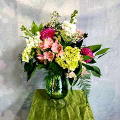 "A vintage mercury glass container holds this romantic collection of summer flowers. A beautiful bouquet, suitable for almost any occasion. The color pallet will remain the same but vase color and seasonal varieties of flowers may vary slightly to give the best look. Approximately 20"" tall and 15"" wide."