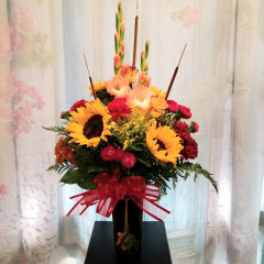 "With Autumn right around the corner this is a perfect bouquet to send to your special someone. Mixed fall bouquet with Glads, carnations, sunflowers, roses, asters and poms in a brown glass vase topped off with cattails...Approx 30"" high **Flowers may change due to availability**"