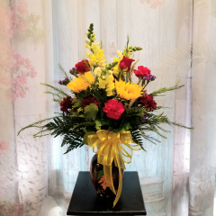 "Featuring our beautiful fall bouquet that can be put on the table for any family gathering. It comes in a brown glass vase with sunflowers, roses, snaps, poms, etc  Approx. 25""H**Flowers may vary depending upon availability**"