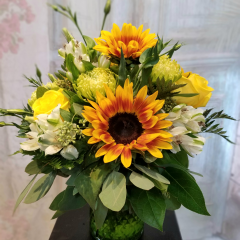 """Three gorgeous sunflowers are captivating in this bouquet, along with green spider poms, yellow roses and ivory blossoms. Approx. 13"""" H x 12"""" W **Colors of flowers and vase may vary**"""