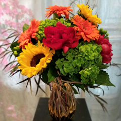 """A Beautiful bouquet of Hydrangea, Peonies, Sunflowers and Gerbera Daisies with fall greens in a light brown mercury vase to adorn any table or coffee table. Approx. 20""""H x 16""""W. **Colors may vary**"""