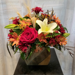 "Our Fall Pumpkin Kisses & Harvest Wishes bouquet is in a keepsake wooden pumpkin container made with roses, lily, fall poms, dyed solidago. An all around arrangement to compliment any table for a nice centerpiece. Approx. 13""H x 12""W"