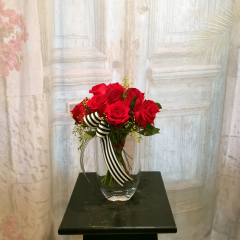 This Dozen Roses Is Arranged In A European Pave Design - Something Simple And Different sprinkled with seeded eucalyptus and finished with a small striped bow. Bouquet is approximately 12 inches tall in a compact design.