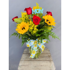 Beautiful combination of roses and sunflowers designed in a clear vase with a sunflower bow and mom pick