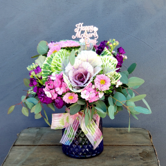 Cute little bouquet with kale, stock, sweet william and asters in a purple vase. **Flowers may be subject to change due to availability***