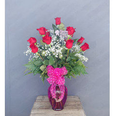 Celebrate Mom with the time honored tradition of long stem red roses! This gorgeous arrangement is filled with a dozen lush Red Roses accented with filler flower and greens.