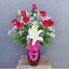 "A beautiful dozen red roses with 4 stems of oriental lilies in a pink vase with a pink polka dot bow and mother's pick. Approx. 29"" H"