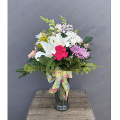 "A lovely bouquet of lilies, snaps, carnations, daisies, etc in a frosted purple glass vase. Approx 26""H x 21""W ***Flowers may be subject to change due to availability***"