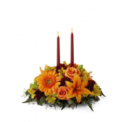 DiBella Flowers & Gifts Las Vegas - Centerpiece spins the magic of the Fall season with each sun-kissed petal to set your gathering space aglow with blooming beauty. Two taper candles are surrounded by a gorgeous arrangement consisting of orange Asiatic Lilies, gerbera daisies, and roses with golden Peruvian Lilies, burgundy cushion poms and assorted greens to create the perfect addition to your Autumn celebration.