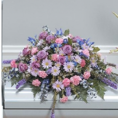 DiBella Flowers & Gifts Las Vegas - Lavender, Blue and Pink Casket Spray CTT69-11 Iris, Delphinium, Daisies,Roses, Carnations, Liatris and more.