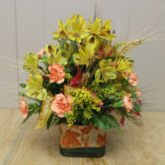 DiBella Flowers & Gifts Las Vegas - Lovely Leaves Cube style vase adorned with fall leave ribbon, wheat, filler, Alstromeria Lilies and Mini Carnation. Perfect for a table centerpiece or just to welcome in Autumn.
