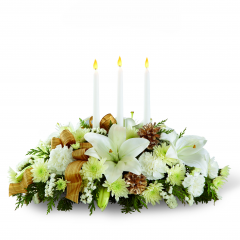 "DiBella Flowers & Gifts Las Vegas - Spirit of the Season Centerpiece blooms with winter elegance and holiday enchantment to grace your Christmas celebrations. White hybrid lilies, carnations, chrysanthemums and statice are arranged amongst holiday greens and accented with pinecones and French wired ribbon for an exquisite look. Arranged to encircle 3 white taper candles, this stunning arrangement will bring a sweet sophistication to your holiday festivities. Approx. 6""H x 19""W by FTD"