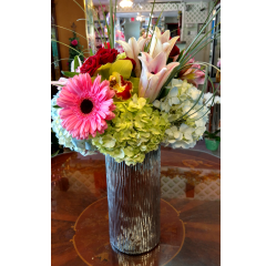 DiBella Flowers & Gifts Las Vegas - Vision of Love Green Hydrangea, Gerbera Daisies, Spray Roses, Alstromeria lilies, Asiatic Lilies, Cymbidium Orchids and Bear Grass accents atop a artfully designed silver keepsake vase.