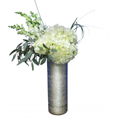 Elegance Snow white Snapdragon, Hydrangea, Seeded Eucalyptus and bear grass in a gold toned, textured cylinder.