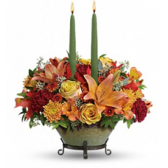 "DiBella Flowers & Gifts Las Vegas - Herald the new season with the magnificent hues of autumn. Arranged in a glorious glazed stoneware bowl with a removable scrolled iron base, this radiant bouquet of golden roses, fiery lilies and slender taper candles brings wondrous warmth to your fall table.his glorious centerpiece includes yellow roses, dark orange asiatic lilies, orange alstroemeria, maroon carnations, brown button spray chrysanthemums, gold cushion spray chrysanthemums, seeded eucalyptus, huckleberry, and oak leaves accented with two taper candles. Delivered in a Tuscan Autumn bowl. Approximately 15 1/2"" W x 16 1/2"" H"