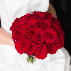 Is there anything more romantic than roses? This bridal bouquet is designed with 24 gorgeous roses in shades of red in a traditional, dome shape. The bouquet is finished with a satin ribbon.  Select 'Bouquet Only' to purchase the bridal bouquet, or select 'w/ Boutonniere' to purchase the bridal bouquet and a matching boutonniere for the groom.