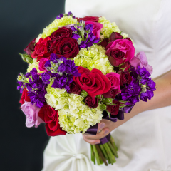 """DiBella Flowers & Gifts Las Vegas - 'Royalty' is a round hand-tied bouquet in a deep and regal color palette. Gorgeous red, hot pink, and lavender roses are accented by pops of green from mini hydrangea. The bouquet is tied with an eggplant satin ribbon.  <p>Select 'Bouquet Only' to purchase the bridal bouquet, or select 'w/ Boutonniere' to purchase the bridal bouquet and a matching boutonniere for the groom.</p>  <p>Bouquet is approximately 10.5"""" in diameter</p>"""