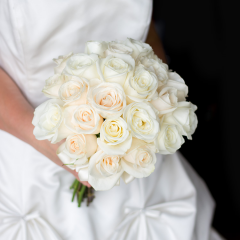 Is there anything more romantic than roses? This bridal bouquet is designed with 25 gorgeous roses in shades of white (white, ivory, cream) in a traditional, dome shape. The bouquet is finished with a white satin ribbon.  Select 'Bouquet Only' to purchase the bridal bouquet, or select 'w/ Boutonniere' to purchase the bridal bouquet and a matching boutonniere for the groom.
