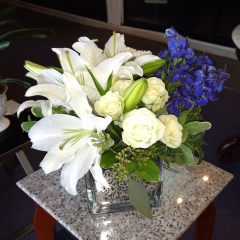 DiBella Flowers & Gifts Las Vegas - White lilies, and roses with a splash of dark blue delphinium in a speckled silver cube. Simple and beautiful.