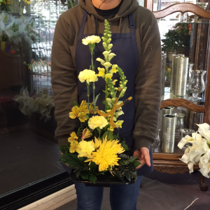 DiBella Flowers & Gifts Las Vegas - Black dish with golden hued flowers. Glittered hockey stick accent included.
