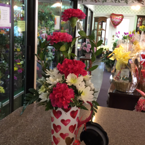 DiBella Flowers & Gifts Las Vegas - Pretty hot pink carnations and fluffy white poms with heart shaped green in keepsake travel mug