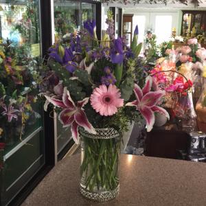 DiBella Flowers & Gifts Las Vegas - Pink stargazers, blue Iris, light pink Gerbera daisies, lavender Larkspar in a filigree cylinder vase.