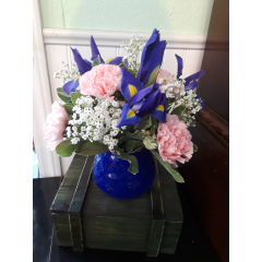 DiBella Flowers & Gifts Las Vegas - A beautiful arrangement with all the classic flowers, iris, carnations and a touch of babies breath in a short blue glass vase.