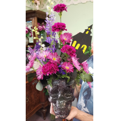 DiBella Flowers & Gifts Las Vegas - Deep fresh purple blooms in a crystal keepsake skull with Halloween decor.