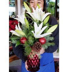 DiBella Flowers & Gifts Las Vegas - Fresh white lilies in red diamond patterned keepsake vase. Christmas green, sparkling ting ting, pine cones and ornaments help make this the prefect Christmas gift.