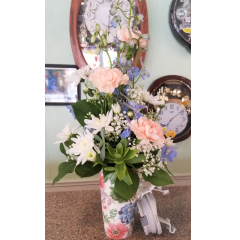 DiBella Flowers & Gifts Las Vegas - Pastel pink,blue and green in keepsake travel mug. Carnations, delphinium,fluffy white poms and succulents added make this a beautiful gift.