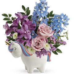 "DiBella Flowers & Gifts Las Vegas - This enchanting arrangement features light pink roses, purple alstroemeria, light blue delphinium, white button spray chrysanthemums, pink sinuata statice, and huckleberry. Delivered in a Charmed Unicorn Keepsake. Approximately 11 1/2"" W x 12 1/2"" H"