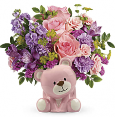 "DiBella Flowers & Gifts Las Vegas - Pink roses, pink spray roses, purple alstroemeria, lavender carnations, lavender stock, and raspberry sinuata statice are arranged with bupleurum and huckleberry. Delivered in a pink Bundle of Love Bear. Approximately 13"" W x 12"" H"