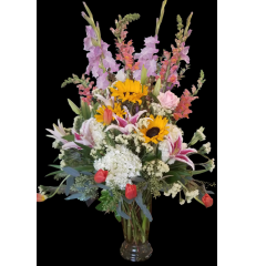 DiBella Flowers & Gifts Las Vegas - fresh airy mix of sunflowers, tulips, lilies, hydrangea and more in clear trumpet vase.
