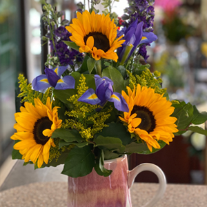 DiBella Flowers & Gifts Las Vegas - Fresh sunflowers, Iris, Larkspur, seasonal greens and filler in keepsake pitcher.