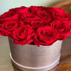 DiBella Flowers & Gifts Las Vegas - Are gorgeous forever roses and silver circular hat box. 12 count.   These are preserved roses that last a year or longer. Our special process preserves REAL roses to last...just like your love! *Ribbon choice can be added to special instructions  * Does NOT include a wristlet- Wristlet must be chosen separately * Red only