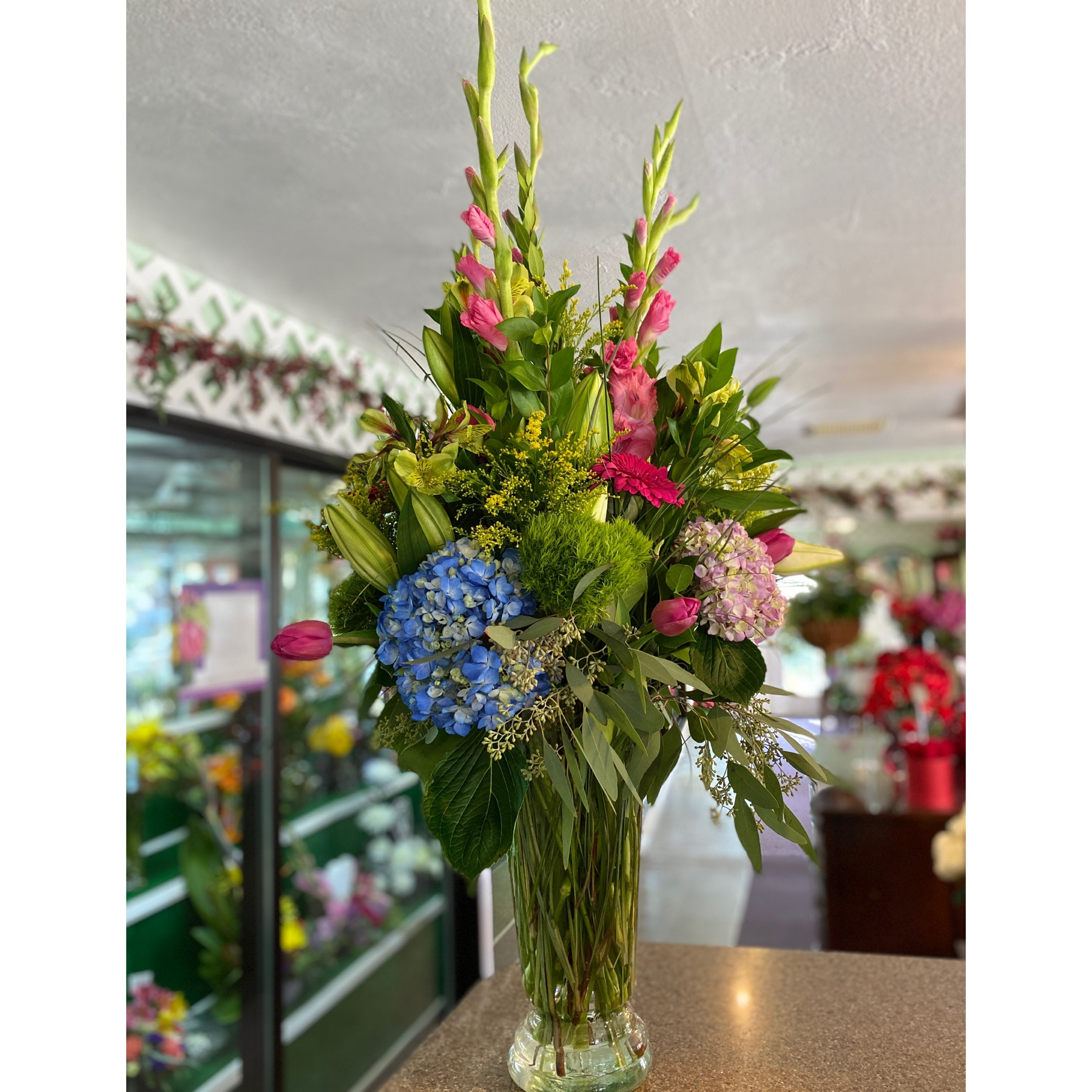 DiBella Flowers & Gifts Las Vegas - Gladiolas, assorted shades of hydrangea, Gerbera daisies, lilies and more and tall trumpet vase perfect for any occasion.