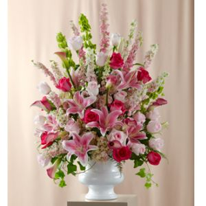 DiBella Flowers & Gifts Las Vegas - The Solemnity Arrangement is the perfect accent piece. Hot pink roses pop against a backdrop of pink roses, larkspur, calla lilies, delphinium, hydrangea, and Oriental Lilies accented with Bells of Ireland and an assortment of fresh, lush greens. Perfectly arranged in a white plastic urn.